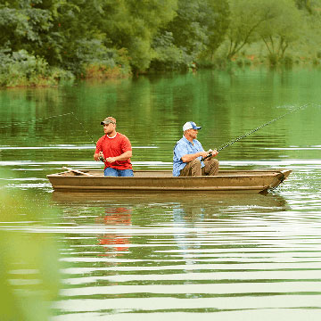 Two men fishing in a canoe on a lake
