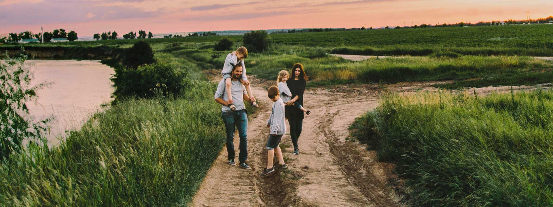 A family walking casually down an empty dirt road at sunset